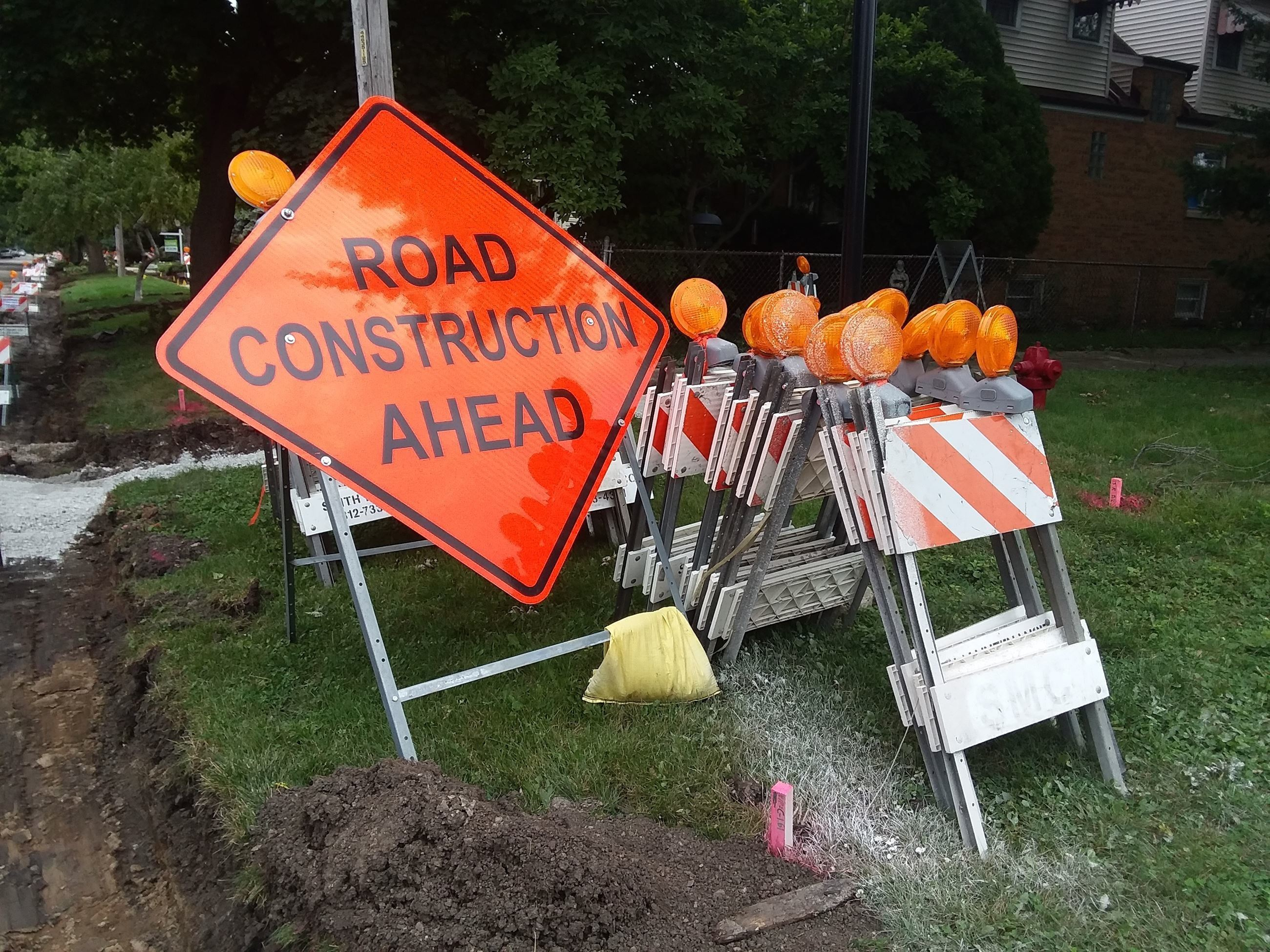 Orange Road Construction sign next to orange and white barricades