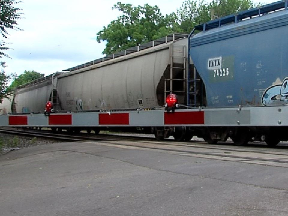 Gray and blue boxcars blocking a street crossing