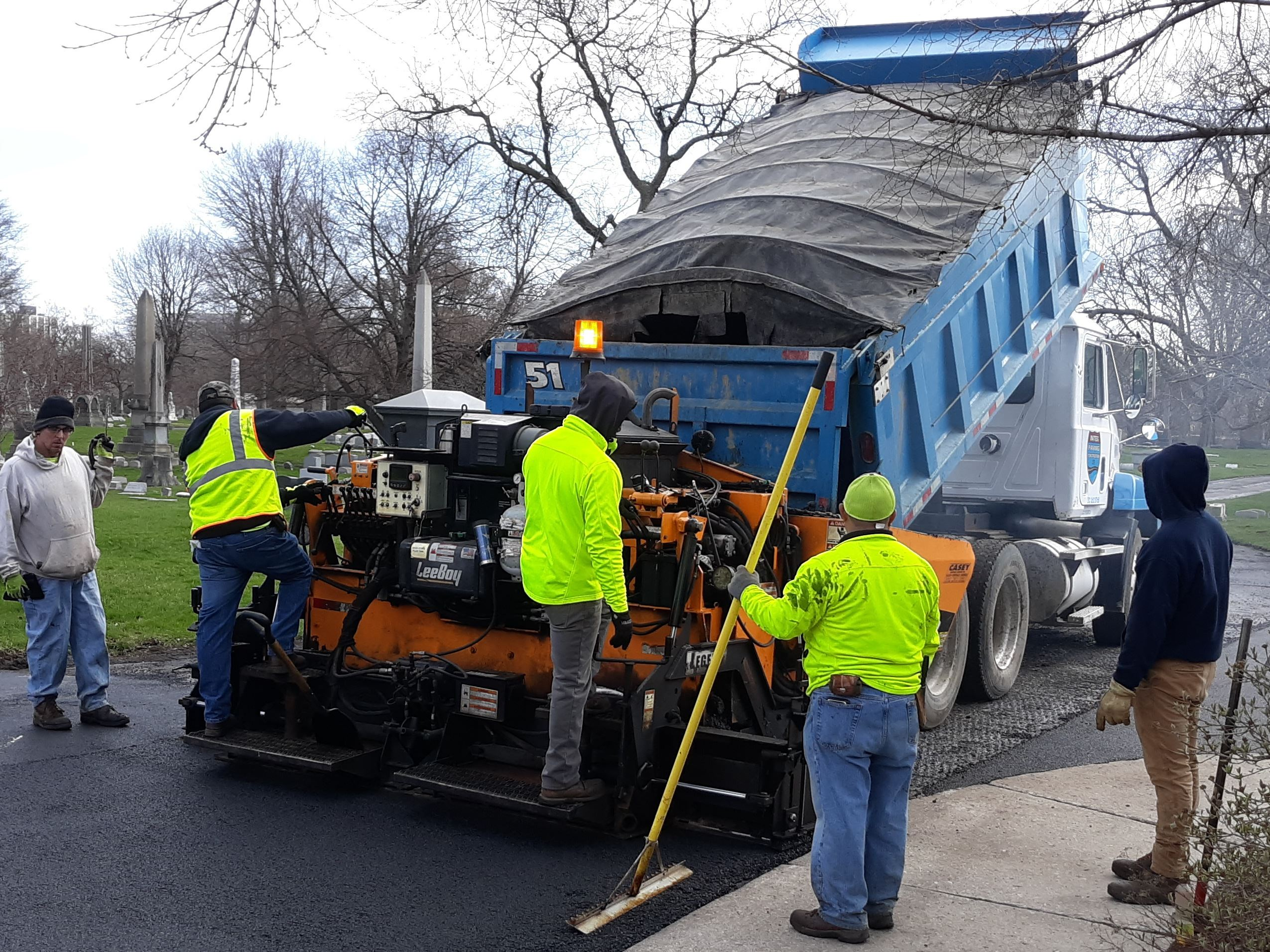Workers using a truck to install a new asphalt road