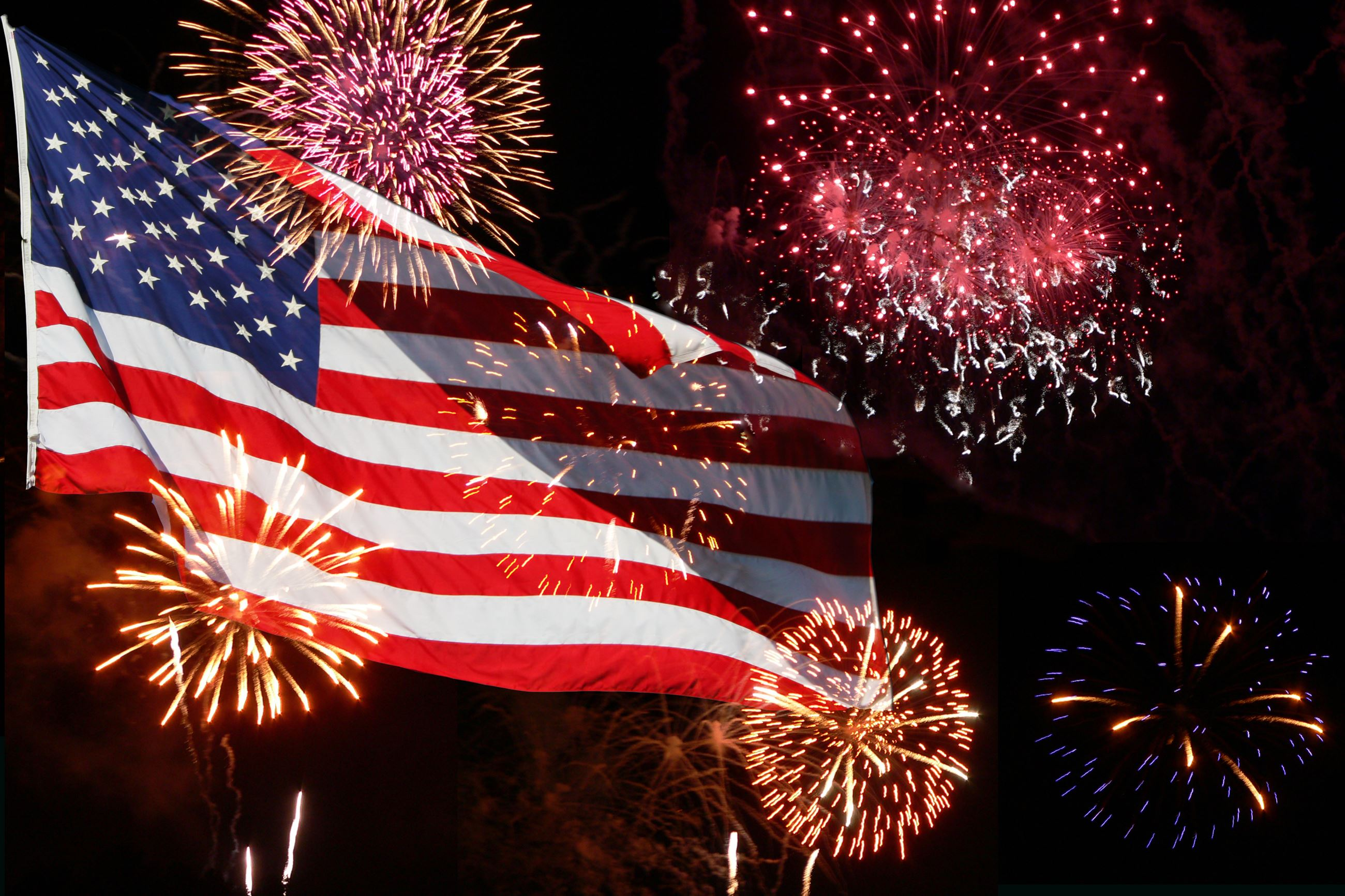 Red, white and blue American flag waving in the sky surrounded by exploding fireworks