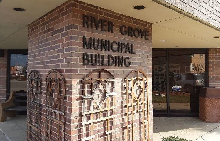 "Brick pillar in front of village hall with ""River Grove"" sign on it"