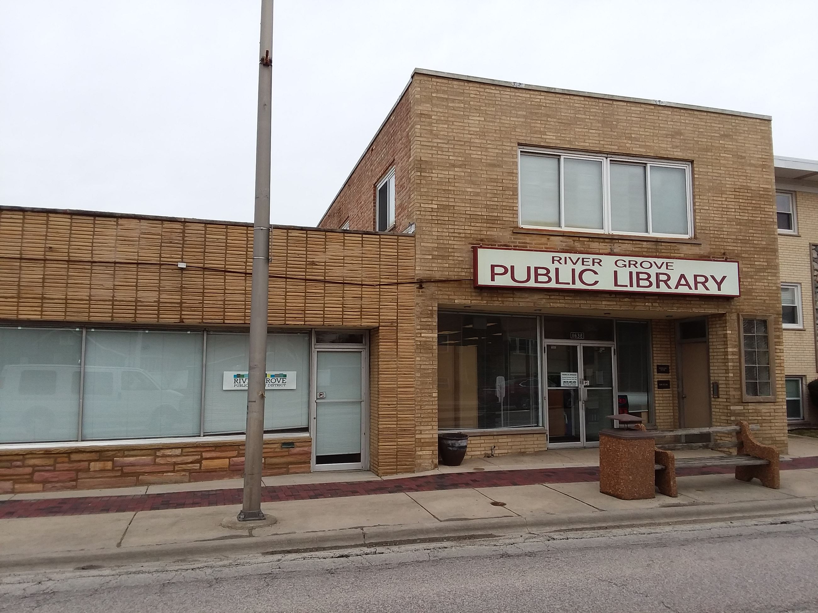 "Exterior view of tan brick building with ""River Grove Library"" sign over front door"