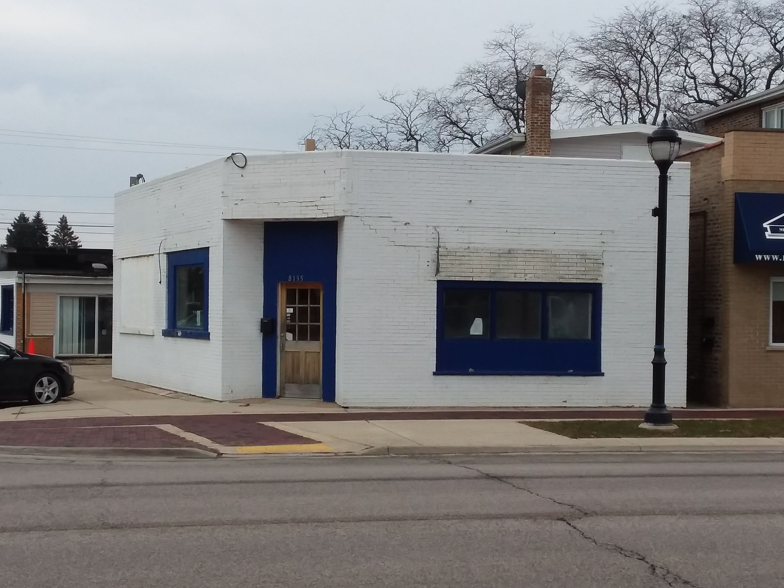 Exterior view of vacant white brick single-story storefront