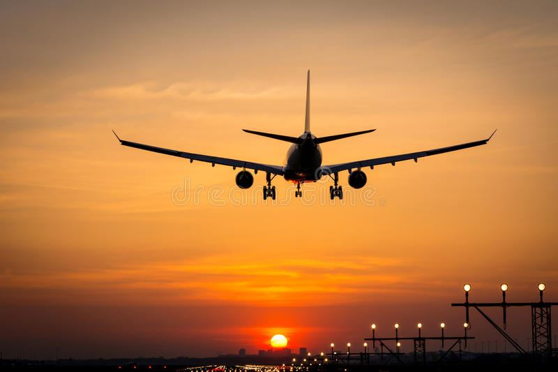 Airplane silhouette landing at sunset
