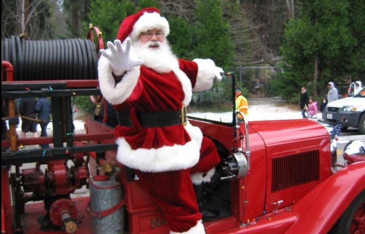 Santa waving while riding on a fire truck