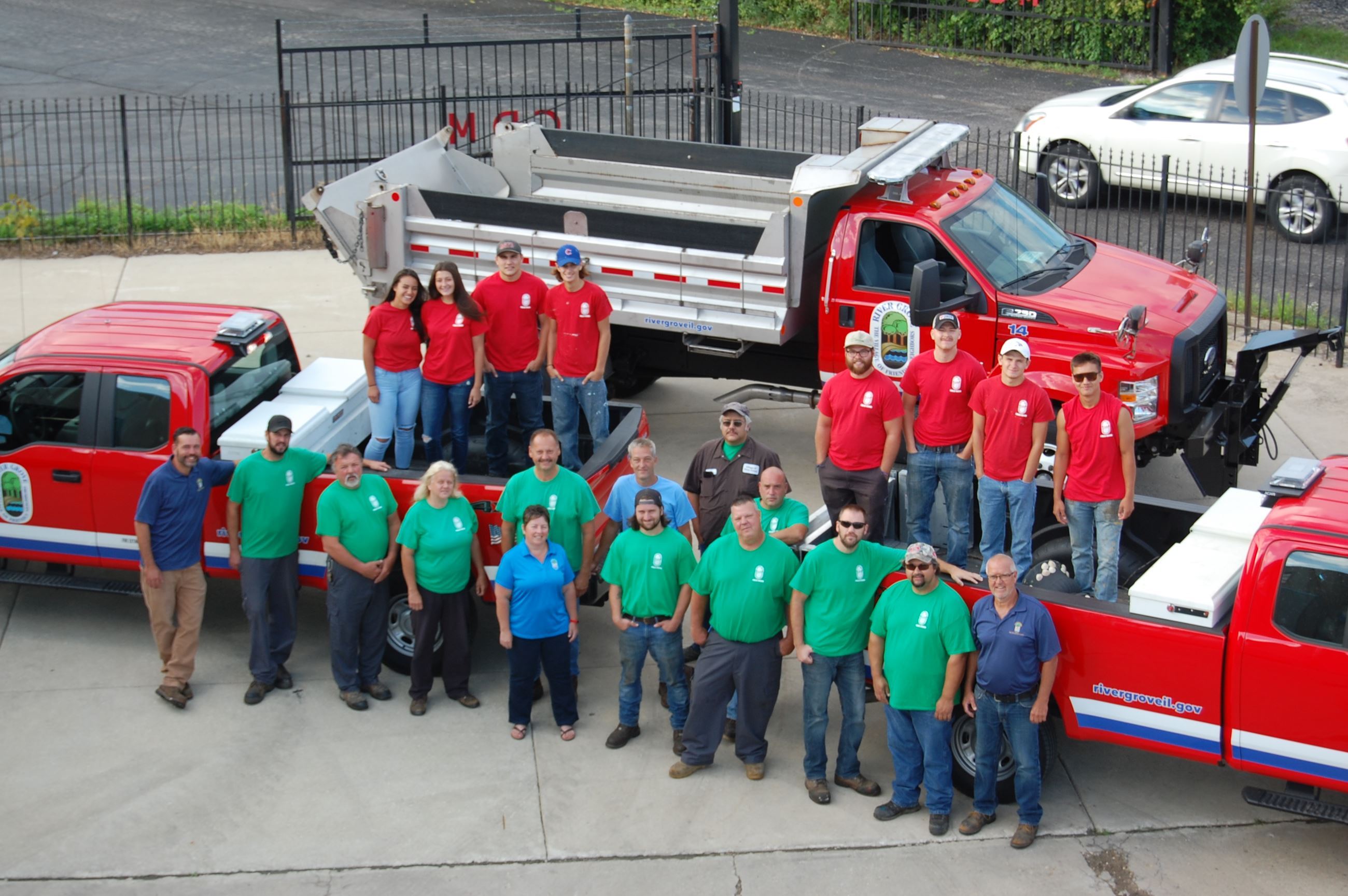 Public Works employees posing in front of their trucks