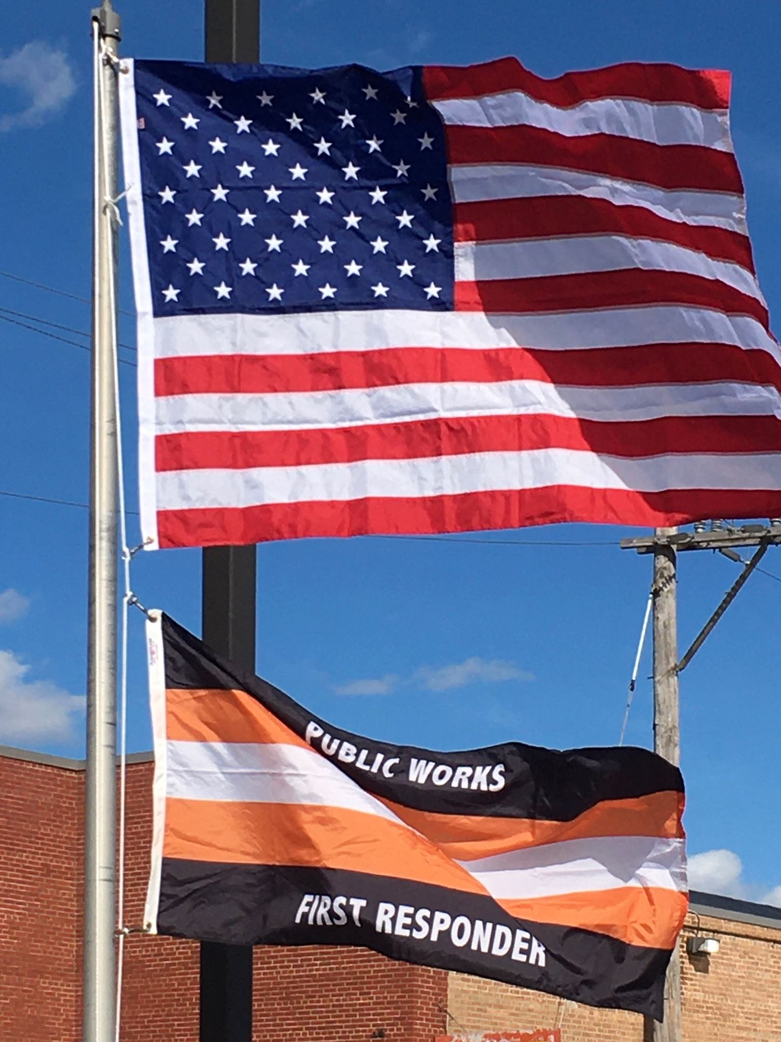 Red, white and blue American flag flying above a white, black and orange public responder flag.